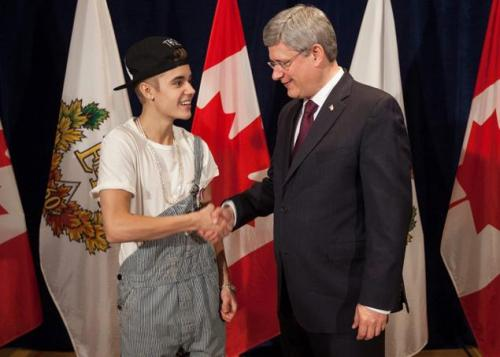 Canadian Prime Minister presenting Justin Bieber with the Diamond Jubilee medal. The medal is awarded to Canadians who have made great achievement abroad.